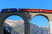 Red train transit on the Landwasser Viaduct, Filisur, Graübunden, Switzerland.
