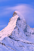 Matterhorn illuminated by the colors of dawn with the Hörnlihütte. Zermatt, Canton of Valais / Wallis, Switzerland.