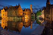 The medieval Belfry and historic buildings reflected in Rozenhoedkaai canal at dusk, Bruges,flemish region, West Flanders, Belgium, Europe