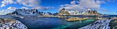 Panorama mit verschneiten Bergen mit Fischerhäuser und Hafen von Hamnoy, Hamnoy, Lofoten, Nordland, Norwegen