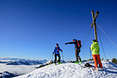 Three persons backcountry skiing standing at the summit of Trainsjoch, Trainsjoch, Bavarian Alps, Upper Bavaria, Bavaria, Germany