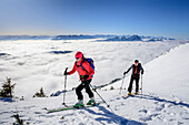 Woman and man backcountry skiing ascending towards Hinteres Sonnwendjoch, fog in the valley, Hinteres Sonnwendjoch, Bavarian Alps, Tirol, Austria