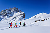 Several persons backcountry skiing ascending towards alpine huts, Geisler range in background, Medalges, Natural Park Puez-Geisler, UNESCO world heritage site Dolomites, Dolomites, South Tyrol, Italy
