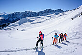 Several persons backcountry skiing ascending to Peitlerkofel, Geisler range in background, Peitlerkofel, Natural Park Puez-Geisler, UNESCO world heritage site Dolomites, Dolomites, South Tyrol, Italy