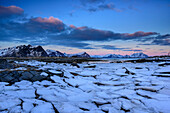 Sheet of ice with snow-covered mountains in background, Lofoten, Nordland, Norway