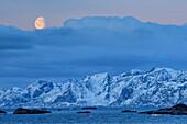 Mond über verschneiten Bergen und Küste, Lofoten, Nordland, Norwegen