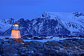 Lighthouse of Gimsoy at dusk with snow-covered mountains in background, Lofoten, Nordland, Norway