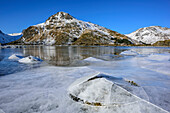 Sheet of ice in fjord with snow-covered mountains in background, Lofoten, Nordland, Norway
