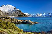Küste mit verschneiten Bergen im Hintergrund, Lofoten, Nordland, Norwegen