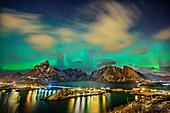 Island near Hamnoy and illuminated houses with polar lights and stary sky, northern lights, aurora borealis, Lofoten, Nordland, Norway