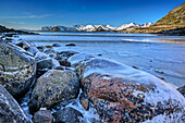 Icy rocks at beach with snow-covered mountains in background, Lofoten, Nordland, Norway