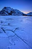 Vereiste Küste mit verschneiten Bergen im Hintergrund, Lofoten, Nordland, Norwegen