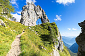 A path leads to Porta di Prada, a rock natural arch in the Grigna group. Grigna Settentrionale(Grignone), Northern Grigna Regional Park, Lombardy, Italy, Europe.