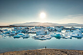 Person admiring icebergs at glacier lagoon of Jokulsarlon. Eastern Iceland, Iceland