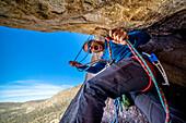 A man belays a technical rock climb in Joshua Tree National Park, California.