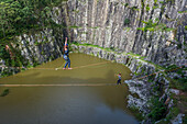 Adventurous man and woman crossing quarry in opposite directions on separate slacklines, Dibs Quarry, Maripora, Sao Paulo State, Brazil