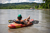 Young man relaxes in whitewater kayak on the Alto (Upper) Madre de Dios river int he jungles of Peru in the Peruvian Amazon. Village of Atalaya in the distance.