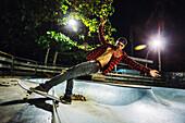 Side view of man skateboarding in illuminated skate park at night, Jimbaran, Bali, Indonesia