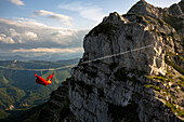 Person sleeping in hammock and hanging on line above mountains in Lower Austria, Austria