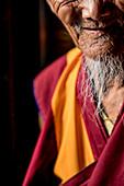 Mid section photograph of smiling senior Buddhist monk with white beard, Boudhanath Temple, Kathmandu, Nepal