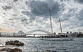 Large white clouds over tourboat sailing in front of Sydney Harbor, Sydney, New South Wales, Australia