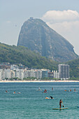 People enjoying a sunny day on a Stand Up Paddle board in Praia de Copacabana, Rio de Janeiro, Brazil