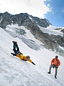In a mountaineering safety training. a student slides down a steep glacier slope trying to arrest himself while the teacher, a mountain guide, is giving advice, Moiry Glacier, Valais, Switzerland