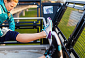 Female runner in sportswear stretching hamstring after jogging near Puget Sound, Seattle, Washington State, USA