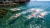 group of seven young swimmers - each with a life buoy - training in the clear and transparent waters of the Ligurian sea with terrace and pontoon behind them and a boat in the background on a sunny day in Paraggi, Cinque Terre, Italy