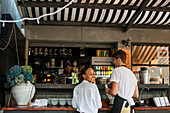 Servers wait at the juice bar at Market, a world-class restaurant at the foot of the Berea in Durban, South Africa. There is a kitchen and dinning inside, as well as a garden caf?? courtyard containing a ring of Leopard trees.