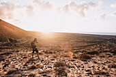 Woman photographing scenery with sand dunes at sunset, Tenerife, Canary Islands, Spain