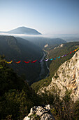 Side view of people lying in hammocks and hanging on high line, Tijesno Canyon, Banja Luka, Bosnia and Herzegovina