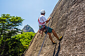Side view of adventurous man rock climbing Morro da Urca next to the Sugarloaf Mountain, Rio de Janeiro, Brazil