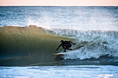 Full length shot of surfer in wetsuit riding wave in sea