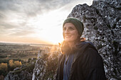 Portrait of young woman in knit hat against rock formation, Polish Jura, Rzedkowice, Silesia, Poland