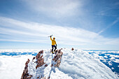 Adventurous mountain climber rising ice pick in victory pose at summit of Mt Shasta, California, USA