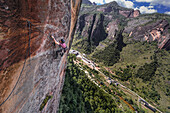 Side view of adventurous rock climber climbing challenging cliff, Liming, Yunnan Province, China