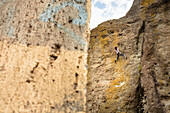 View of adventurous rock climber climbing challenging cliff, Mexico