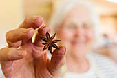 Smiling senior woman holding Anise Star which is used in cooking, Fort Collins, Colorado, USA