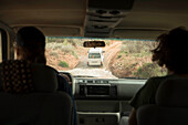 Rear view of two men driving down dirt road to go rock climbing, Moab, Utah, USA