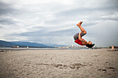 Man doing backflip in mid-air while doing acroyoga at beach
