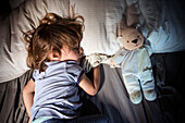 Overhead view of young girl sleeping with teddy bear in bed