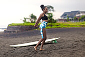 Side view shot of single woman with surfboard at beach