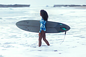 Side view shot of single woman with surfboard in sea