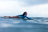 Side view shot of woman paddling on surfboard in sea