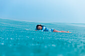 Smiling woman lying on surfboard in sea