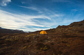 Greenland offers some of the most spectacular landscape to explore and camp within here, a lone tent is set up in the autumn-clad hills of Disko Island