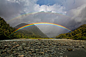 Double rainbow against large clouds over rocky valley, New Zealand