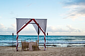 Fancy dinner table with awning on beach for romantic dinner by ocean, Puerto Morelos, Yucatan Peninsula, Mexico