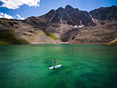 Aerial view of young male fly fishing from his paddle board on high alpine lake in Aspen, Colorado, USA